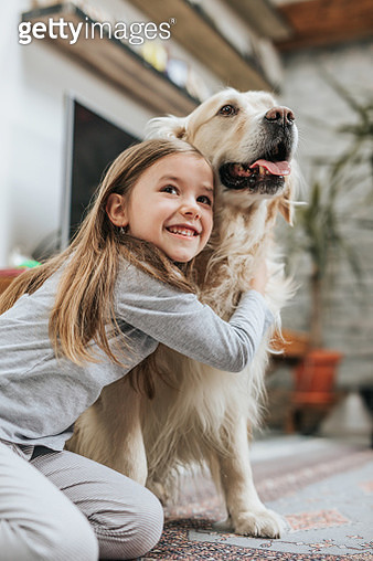 Happy girl embracing her retriever at home. - gettyimageskorea