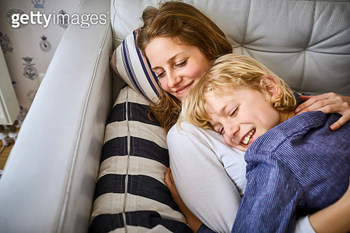 Happy mother cuddling with son on sofa - gettyimageskorea