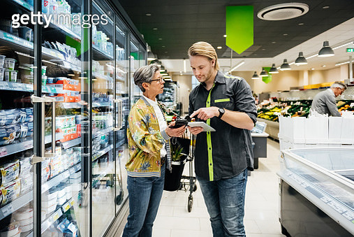 A grocery store clerk assisting a woman with a query about a product in her local supermarket. - gettyimageskorea