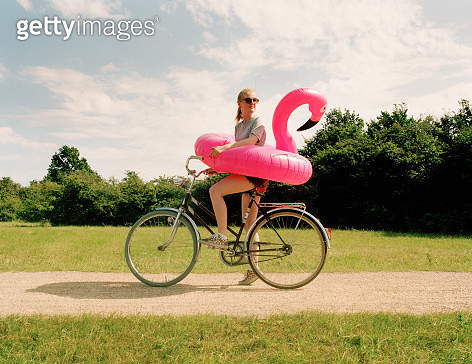 Young woman sitting on bicycle with pink flamingo swim ring, looking back. - gettyimageskorea