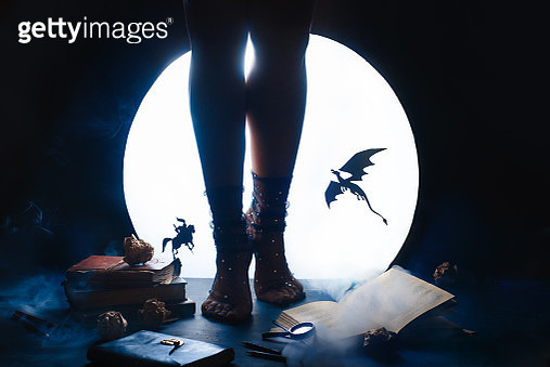 A young female writer with a fairy tale book. Dragon and Knight silhouettes against shiny Moon background. Legs in starry socks - gettyimageskorea