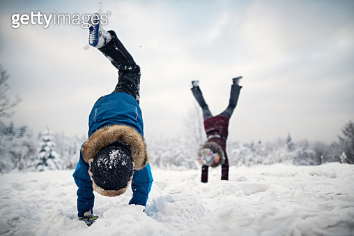 Little boy and his elder sister are enjoying the snow and the winter. Kids are doing handstands. Shot with Nikon D850 on cold winter day evening. - gettyimageskorea