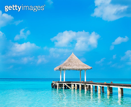 Thatched gazebo and dock on tropical ocean - gettyimageskorea