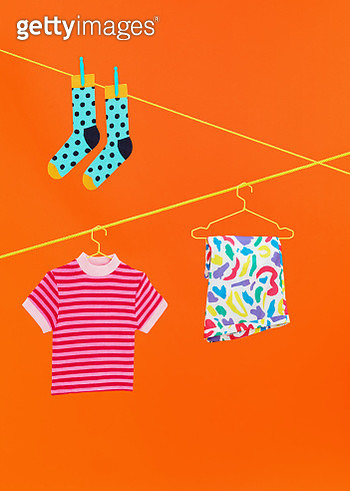 Studio still life image of blue socks, stripy t-shirt and colourful shorts hanging on a yellow washing line shot on orange background. - gettyimageskorea