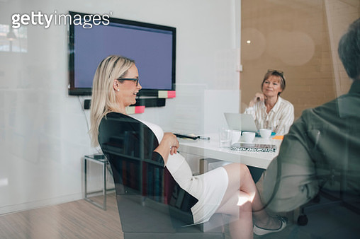 Pregnant businesswoman sitting with colleagues in board room seen from glass - gettyimageskorea