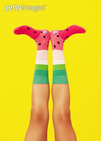 Studio shot of two legs and feet wearing socks that resemble a flamingo beak shot on yellow background. - gettyimageskorea