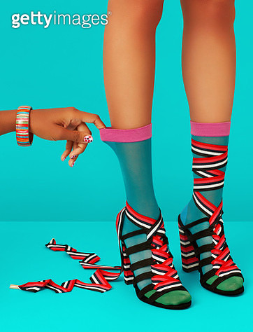 Woman wearing socks and high heels with hand reaching in to pull on sock. - gettyimageskorea