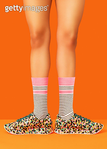 Studio shot of woman standing with turned out feet wearing trainers and socks shot on orange background. - gettyimageskorea