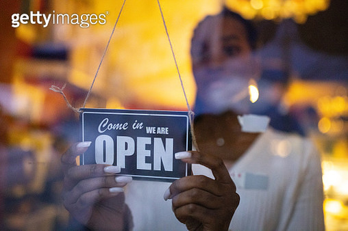 Business owner hanging an open sign at a cafe - gettyimageskorea
