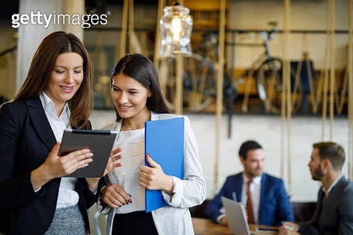 Two young businesswomen discussing business strategy using digital tablet - gettyimageskorea