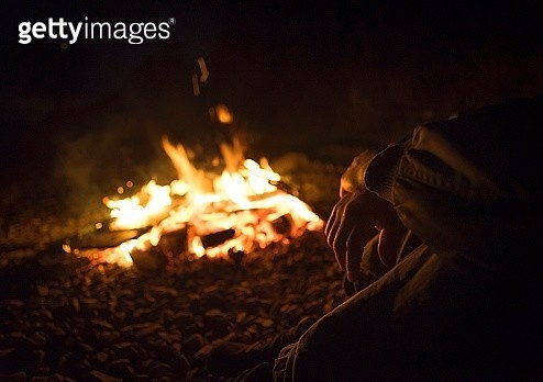 Low Section Of Man Sitting By Campfire At Night - gettyimageskorea