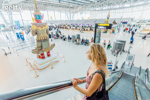 Young woman travels through airport lobby - gettyimageskorea