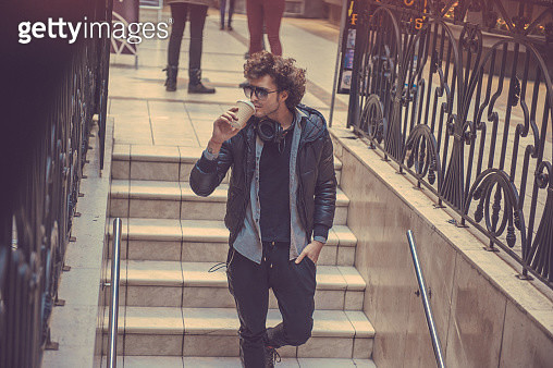 young man walking downstairs with a cup of coffee - gettyimageskorea
