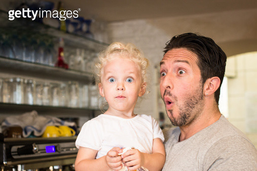 Little girl (two years old) and her father making funny astonished faces. In the background part of small cafe. - gettyimageskorea