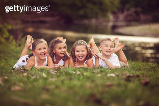 laughing children lying on grass - gettyimageskorea