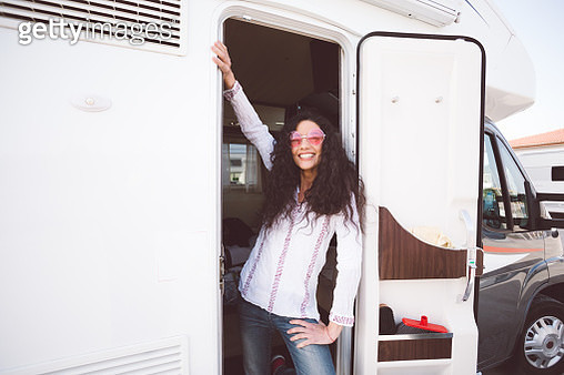 Smiling hippie woman staring from the campervan - gettyimageskorea
