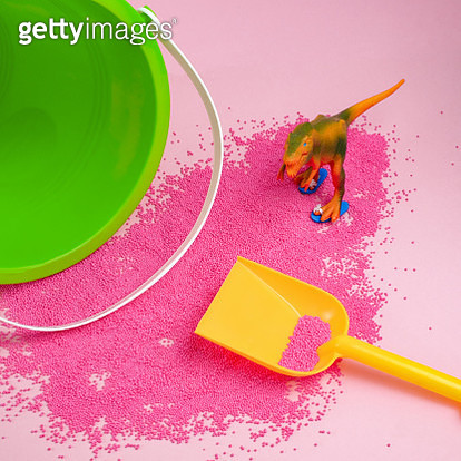 Toy dinosaur with beach pail and shovel playing in pink sand. - gettyimageskorea