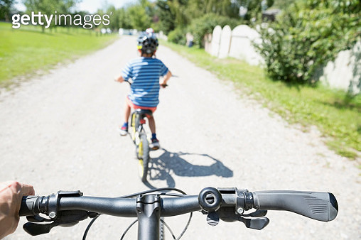 Personal perspective following boy riding bicycles on sunny road - gettyimageskorea