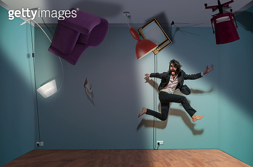 Elegant man jumps and runs away from an upside-down room.Digital composite - gettyimageskorea