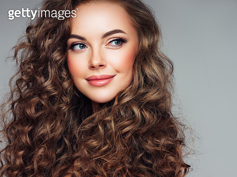 Young woman with brown voluminous and curly hair - gettyimageskorea