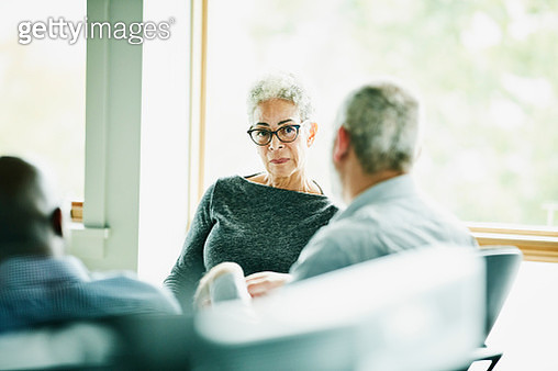 Senior businesswoman listening to presentation from coworker during meeting in office - gettyimageskorea