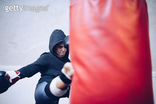 Young female kickboxer kicking punching bag at gym - gettyimageskorea