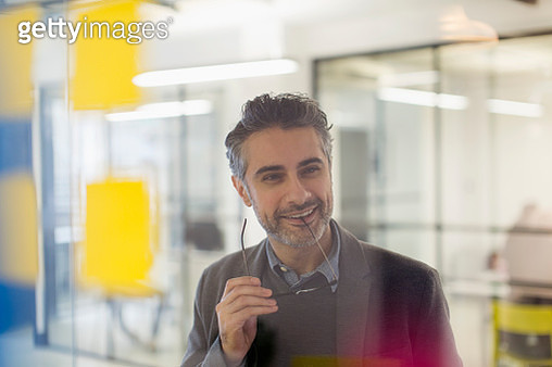 Confident, smiling creative businessman brainstorming in office - gettyimageskorea