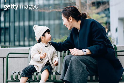 A loving young Asian mother and lovely little daughter sitting on a bench on the urban balcony, looking at each other chatting. Enjoying mother and daughter bonding time in a relaxing afternoon - gettyimageskorea
