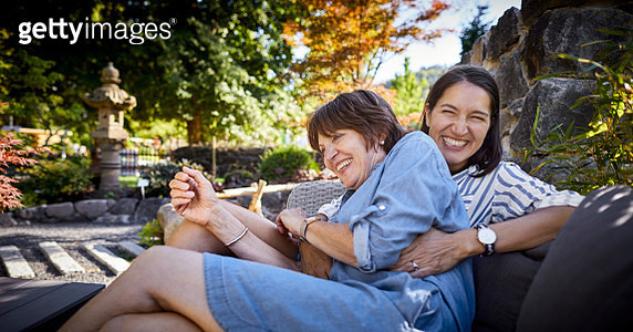 Happy senior woman and adult daughter sitting on a couch in garden - gettyimageskorea