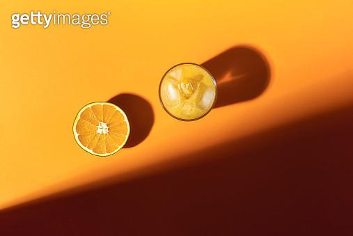 Orange Juice Glass With Ice And Half Of Orange Fruit, In Sunlight. Citrus Fruit On Orange Background - gettyimageskorea