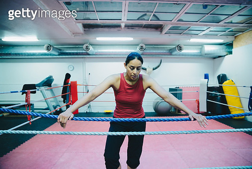 Mid adult female athlete leaning on boxing ring rope at health club - gettyimageskorea
