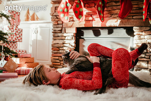 Boy lying on a fluffy rug stroking his cat - gettyimageskorea