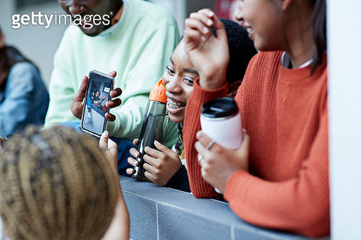 Cheerful friends enjoying with photograph on smart phone at college campus - gettyimageskorea