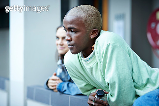 Young man with short hair looking away while leaning on retaining wall at university campus - gettyimageskorea