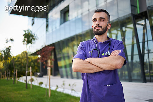 Confident male nurse with crossed arms standing in front of modern hospital - gettyimageskorea