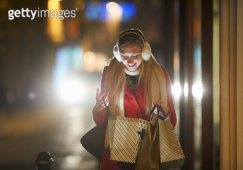 A woman looks into her shopping bag on a high street at night. - gettyimageskorea