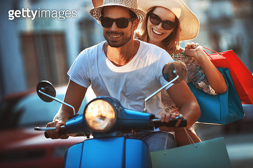 Couple on a scooter bike coming home from shopping. - gettyimageskorea