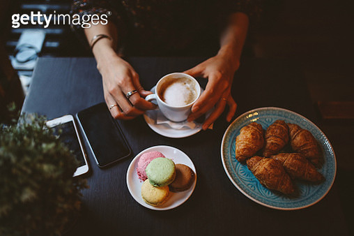 Woman having a coffee and sweets in the cafe - gettyimageskorea