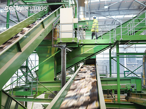Worker checking conveyor belts with waste paper in waste recycling plant. - gettyimageskorea