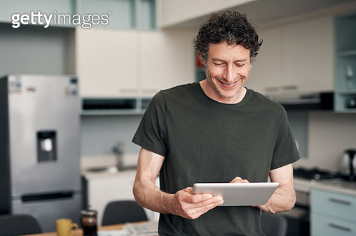 Shot of a mature man using a digital tablet at home - gettyimageskorea