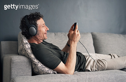 Shot of a mature man wearing headphones and using a cellphone while relaxing at home - gettyimageskorea