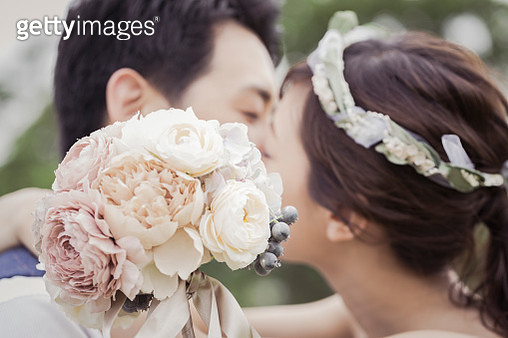 Bride and groom kissing in the green field - gettyimageskorea