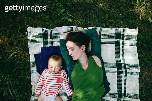 Mother and baby having a nap together on lawn - gettyimageskorea