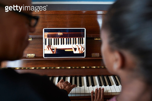 Grandmother teaching piano to grandchild - gettyimageskorea
