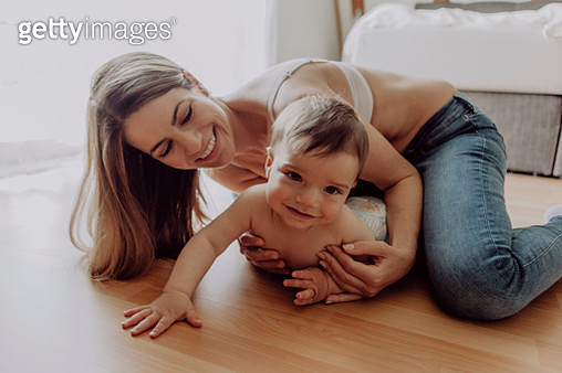 mother and baby son playing and crawling on floor - gettyimageskorea