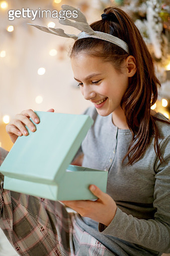 Teenage girl in pajamas opening the Christmas gift box lid with a smile - gettyimageskorea