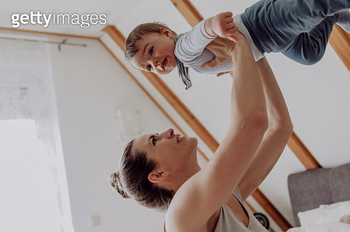 Mother playing with her baby son at home - gettyimageskorea