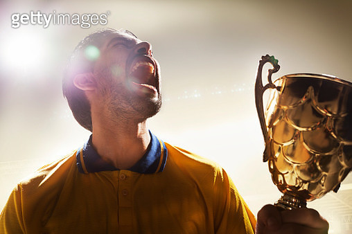 Athlete holding trophy cup in stadium - gettyimageskorea