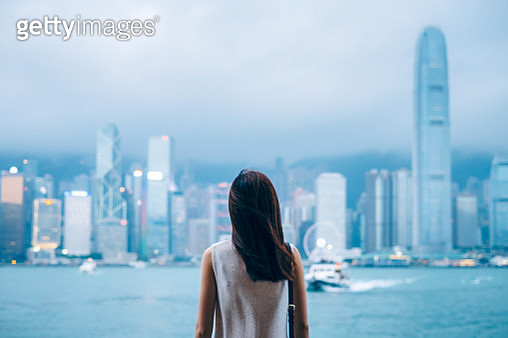Rear view of female traveller enjoys the view at Victoria Harbour and Hong Kong city skyline at dusk - gettyimageskorea