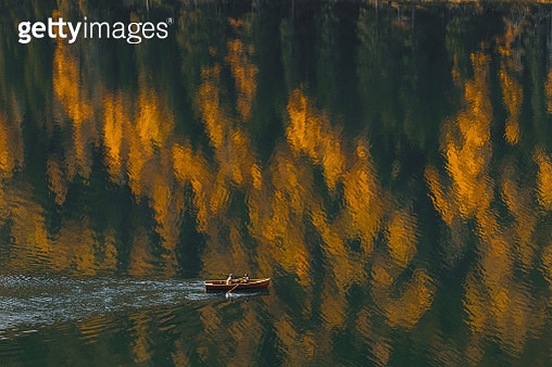 Aerial view of boat sailing by beautiful autumn lake with forest reflection in water - gettyimageskorea